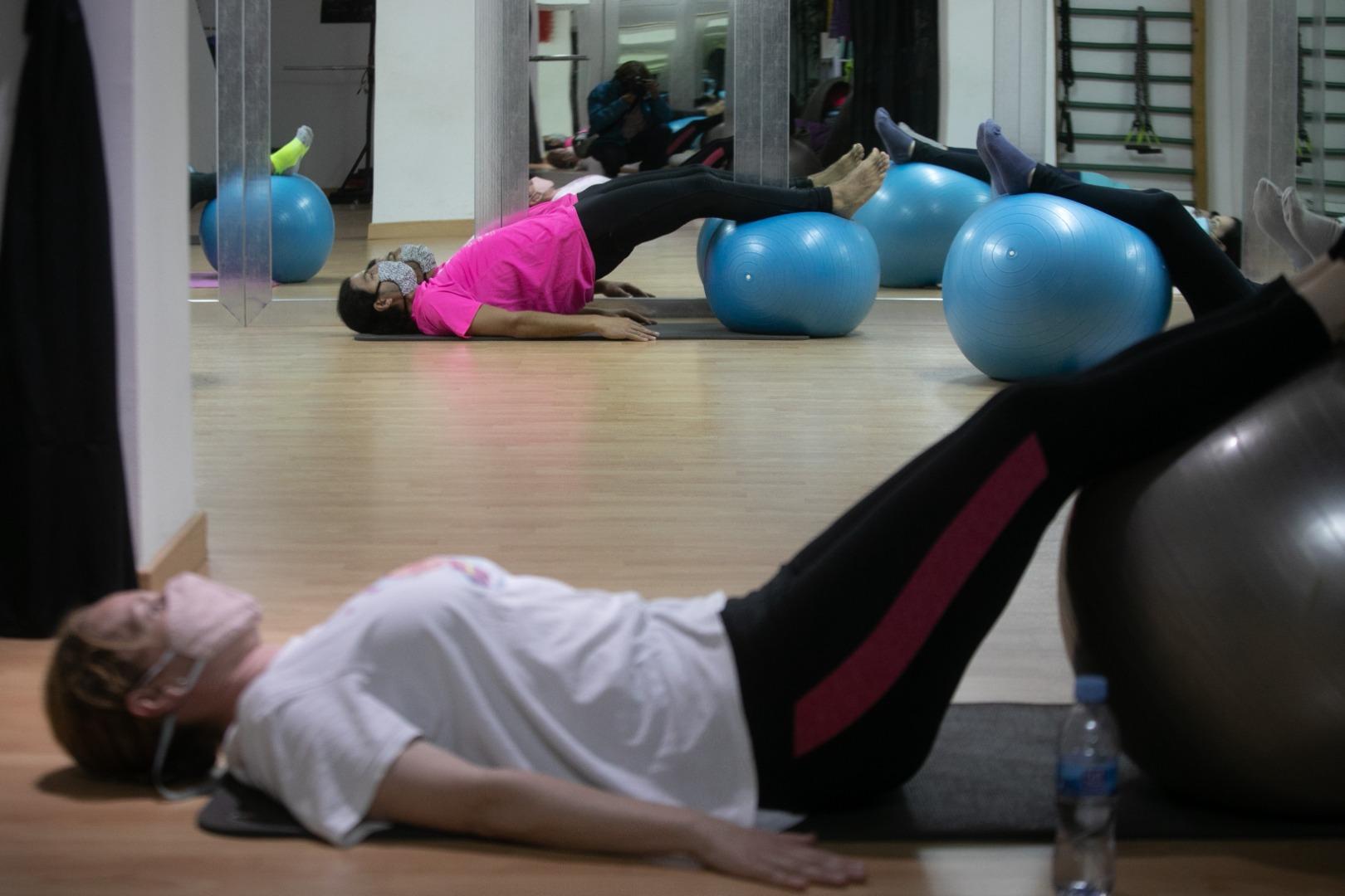 mujer haciendo pilates en el suelo con pelota